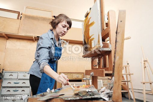 istock Young beautiful woman painter among easels and canvases in a bright studio. 1145251287