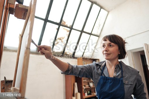 istock Young beautiful woman painter among easels and canvases in a bright studio. 1145251310