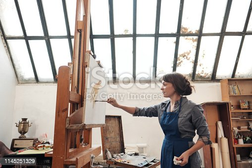 istock Young beautiful woman painter among easels and canvases in a bright studio. 1145251329