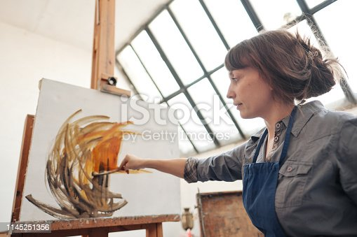 istock Young beautiful woman painter among easels and canvases in a bright studio. 1145251356