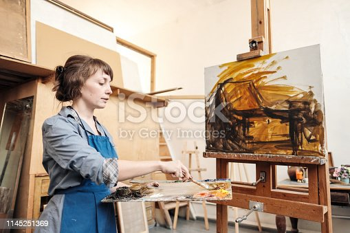 istock Young beautiful woman painter among easels and canvases in a bright studio. 1145251369