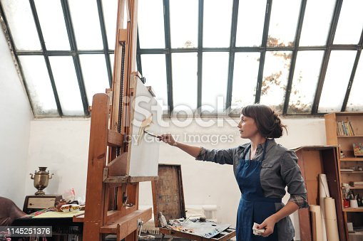 937313030 istock photo Young beautiful woman painter among easels and canvases in a bright studio. 1145251376