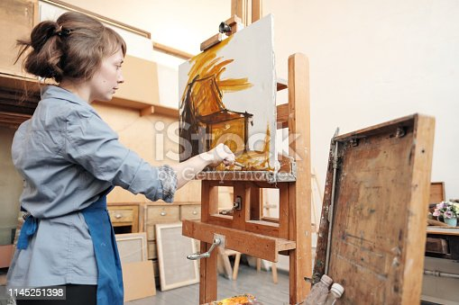 937313030 istock photo Young beautiful woman painter among easels and canvases in a bright studio. 1145251398