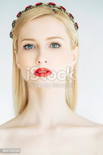 Studio shot of young beautiful woman on light background. Professional make up and hair style.