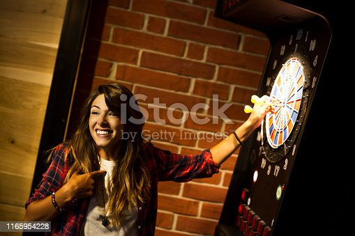 istock Young beautiful woman playing darts in a club and smiling 1165954228