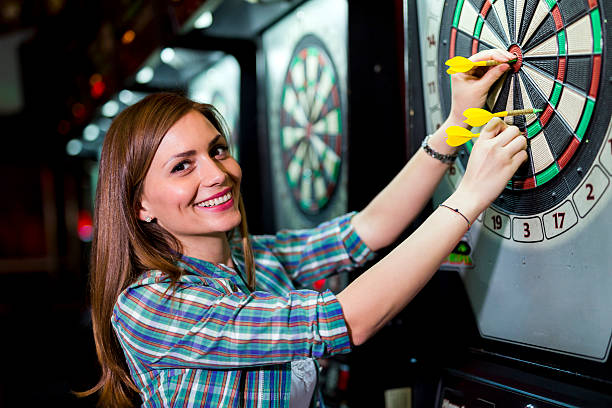 Young beautiful woman playing darts in a club stock photo
