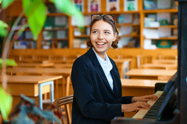 young beautiful woman playing the piano in class stock photo