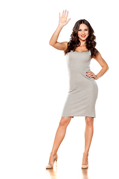 young beautiful woman posing in a short dress waving hand - mini dress stock photos and pictures