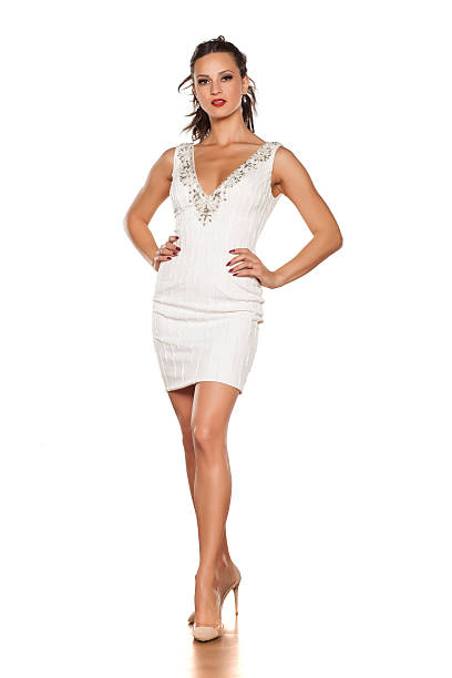 young beautiful woman posing in a white short dress - mini dress stock photos and pictures