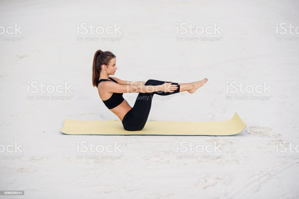 Young beautiful woman practicing yoga, doing press ups exercise on the beach of the sea. stock photo