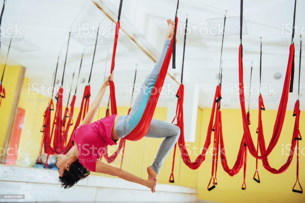 Young beautiful woman practicing yoga Fly with a hammock in the bright studio. The concept of mental and physical health. stock photo