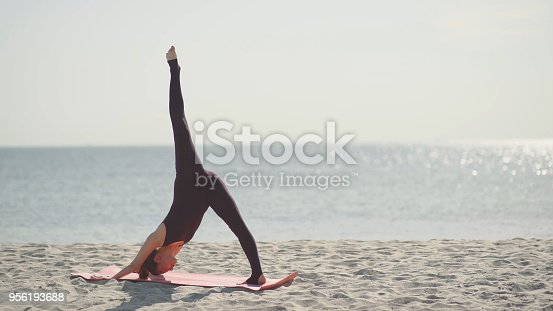 816941230 istock photo Young beautiful woman practicing yoga on the beach at sunny day. Healthy active lifestyle concept 956193688