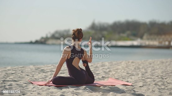 816941230 istock photo Young beautiful woman practicing yoga on the beach at sunny day. Healthy active lifestyle concept 956193724