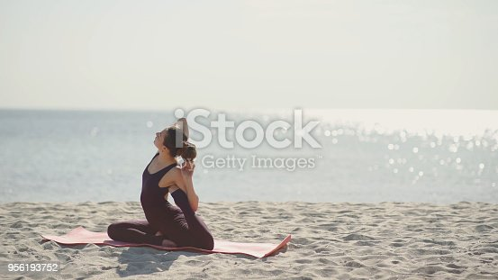 816941230 istock photo Young beautiful woman practicing yoga on the beach at sunny day. Healthy active lifestyle concept 956193752