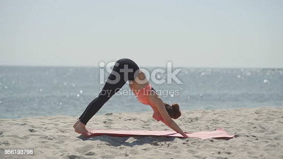 816941230 istock photo Young beautiful woman practicing yoga on the beach at sunny day. Healthy active lifestyle concept 956193798