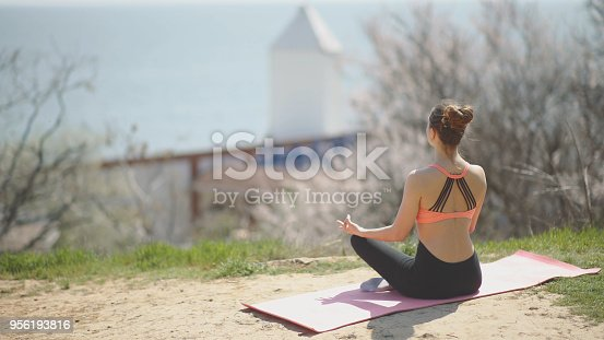 816941230 istock photo Young beautiful woman practicing yoga on the beach at sunny day. Healthy active lifestyle concept 956193816