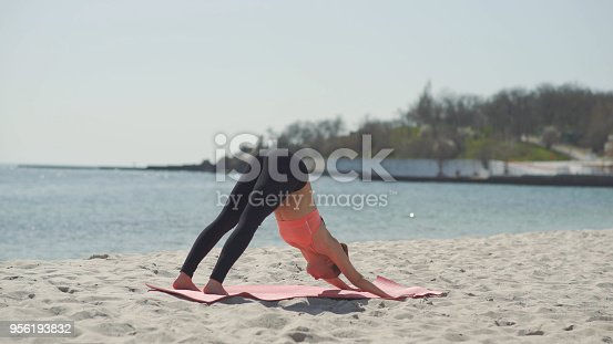816941230 istock photo Young beautiful woman practicing yoga on the beach at sunny day. Healthy active lifestyle concept 956193832