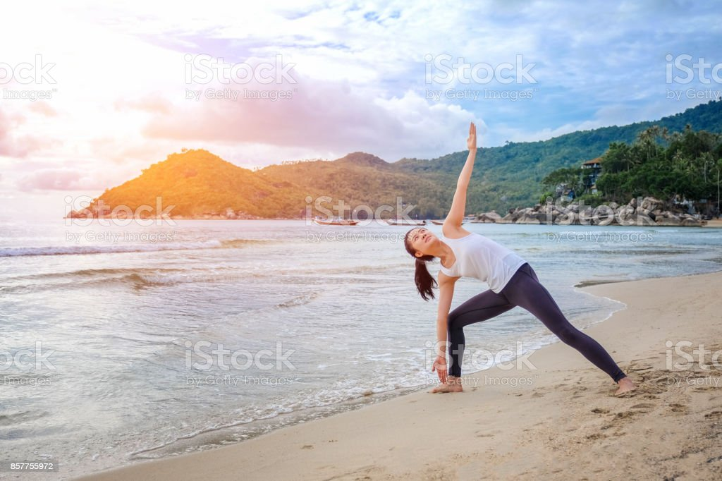 Young beautiful woman practicing yoga on the beach at sunrise stock photo