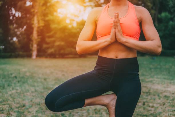 mooie jongedame beoefenen van yoga buiten - verduisterd gezicht stockfoto's en -beelden