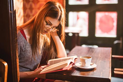 若い美しい女性の読書はカフェ - 1人のストックフォトや画像を多数ご用意