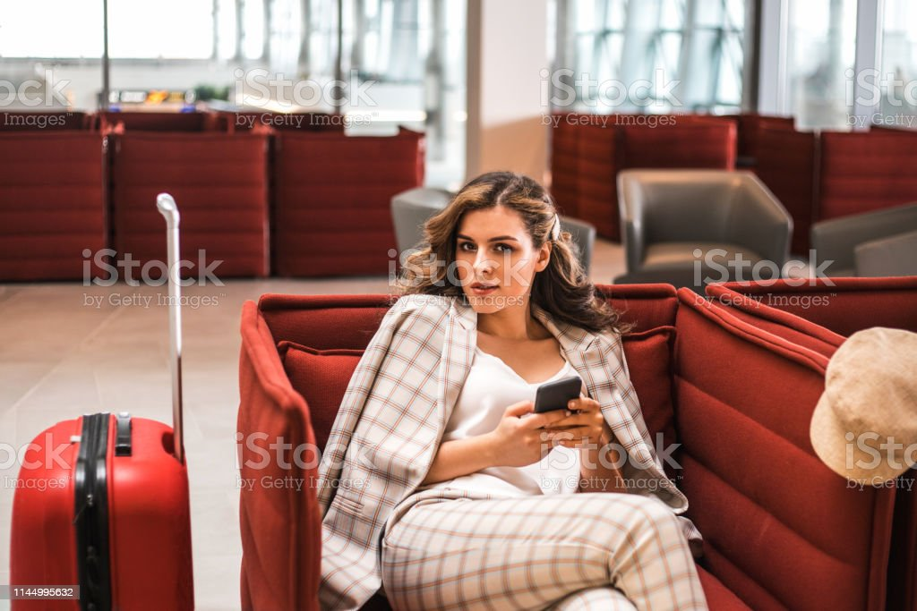 Young beautiful businesswoman reading phone messages in Airport...