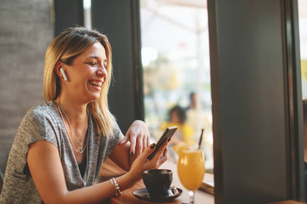 Young beautiful woman relaxing in coffee shop and having video chat via smartphone and drink coffee. stock photo