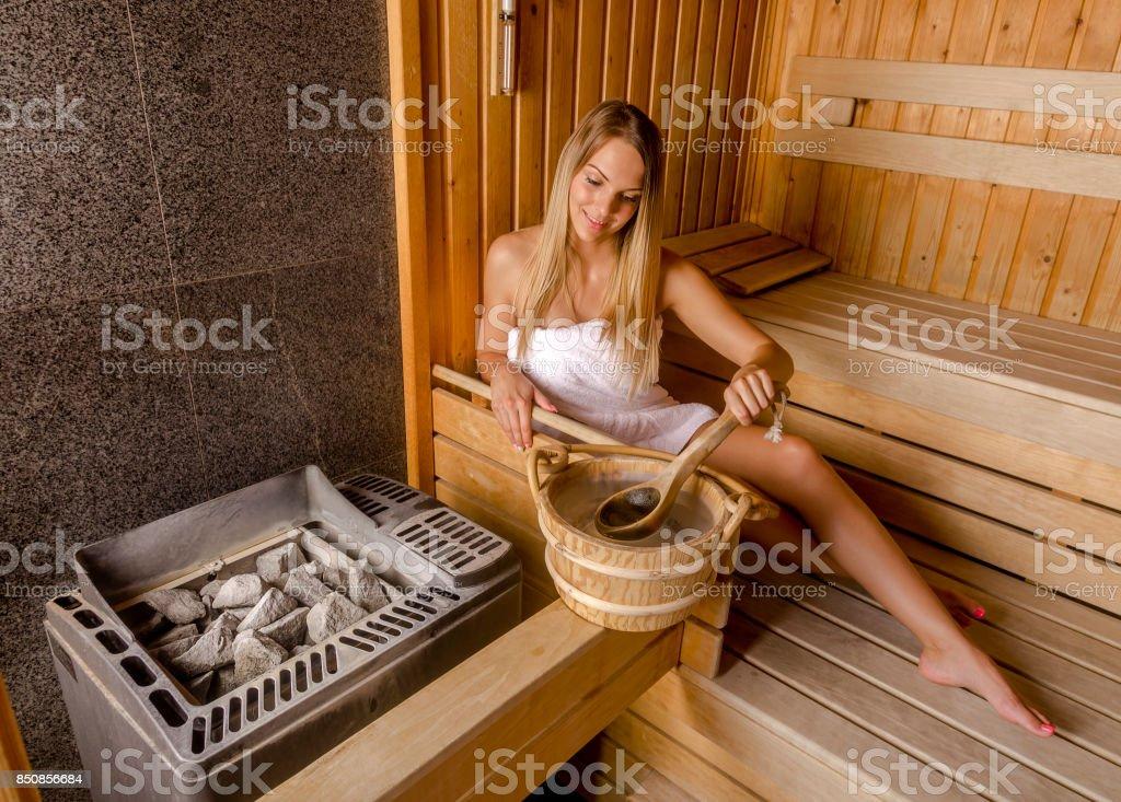 Young beautiful woman relaxing in the sauna. stock photo