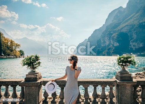 istock Young beautiful woman relaxing on picturesque Garda Lake 670983934