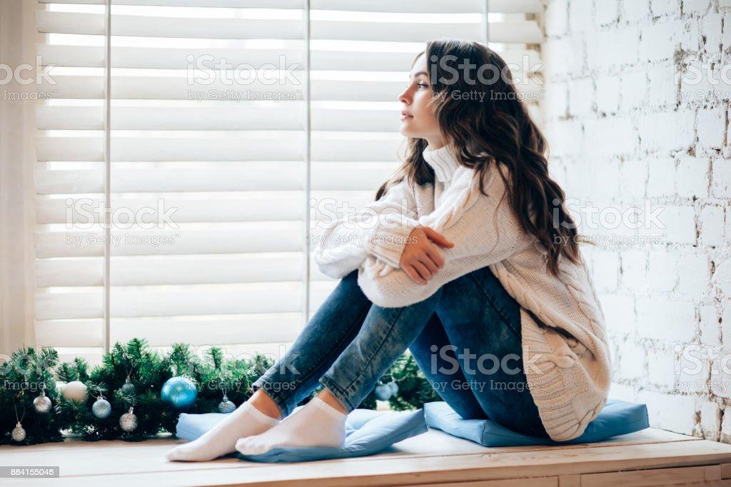 Junge schöne Frau, die entspannend auf die Fensterbank in Weihnachten dekoriert nach Hause. – Foto