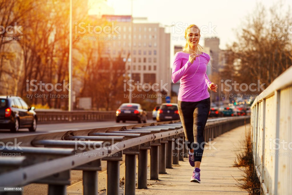 Young beautiful woman running on the sidewalk besides traffic road in the city stock photo