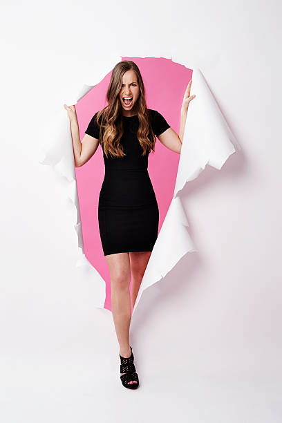 Young beautiful woman screaming to escape form paper stock photo