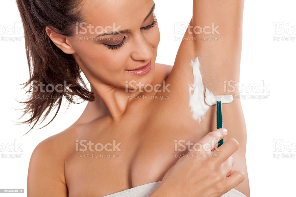 Young beautiful woman shaving her armpits stock photo