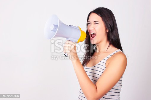 istock Young beautiful woman shouting through a megaphone 597223300