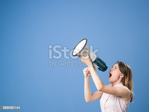 istock Young Beautiful Woman Shouting Through Megaphone On Sky Blue Background 588585144
