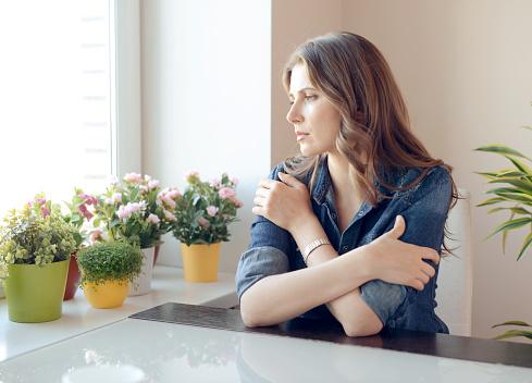 若い美しい女性のテーブルに座る - 1人のストックフォトや画像を多数ご用意