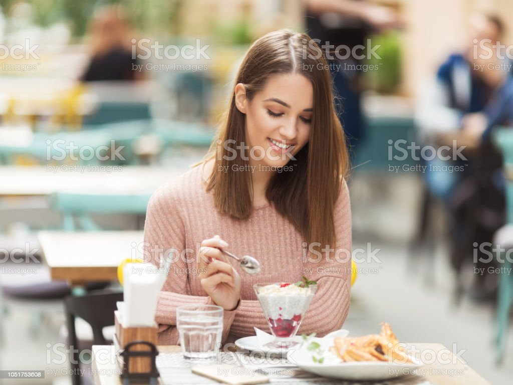 Young beautiful woman sitting in a cafe outdoors and eating salad stock photo