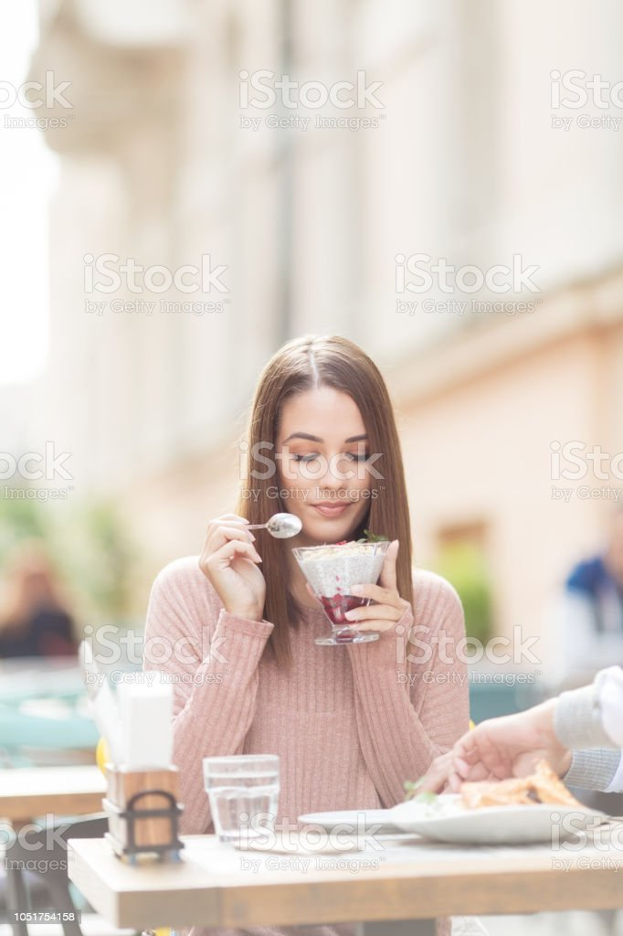 Young beautiful woman sitting in a cafe outdoors and having a launch break stock photo