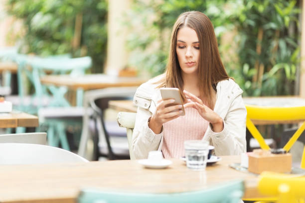 Young beautiful woman sitting in a cafe outdoors and using smart phone stock photo