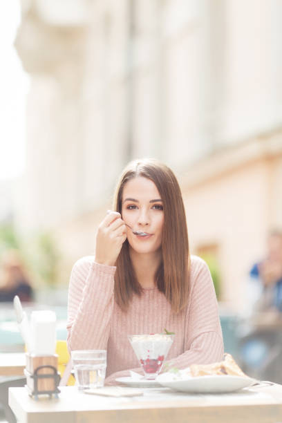 Young beautiful woman sitting in a cafe outdoors,eating salad and posing for a camera stock photo