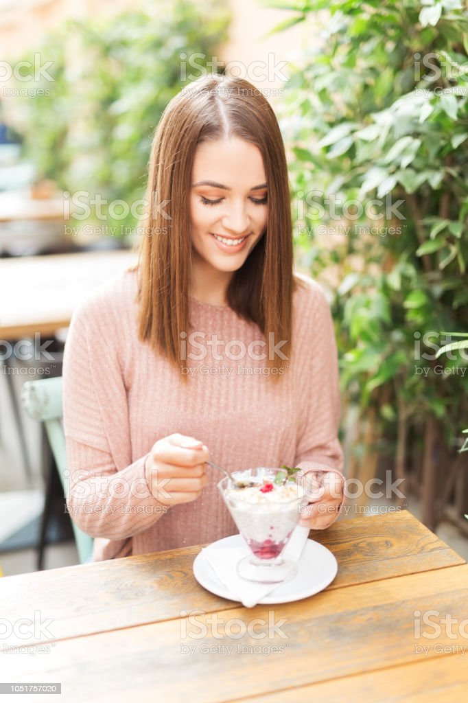 Young beautiful woman sitting in a cafe outdoors,eating salad and smiling in front of a camera stock photo