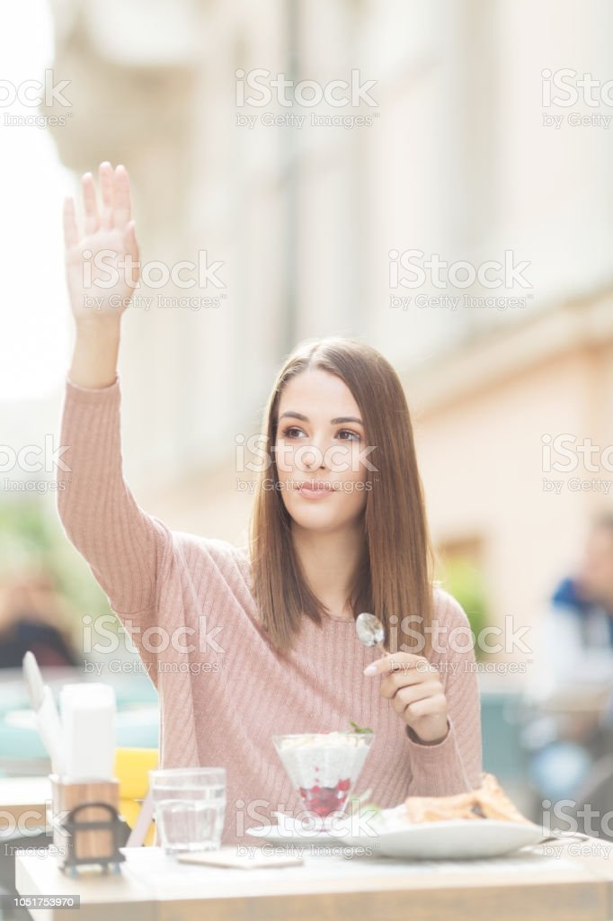 Young beautiful woman sitting in a cafe outdoors,eating salad and calling waiter stock photo