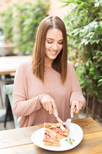 Young beautiful woman sitting in a cafe outdoors,eating salad and smiling stock photo