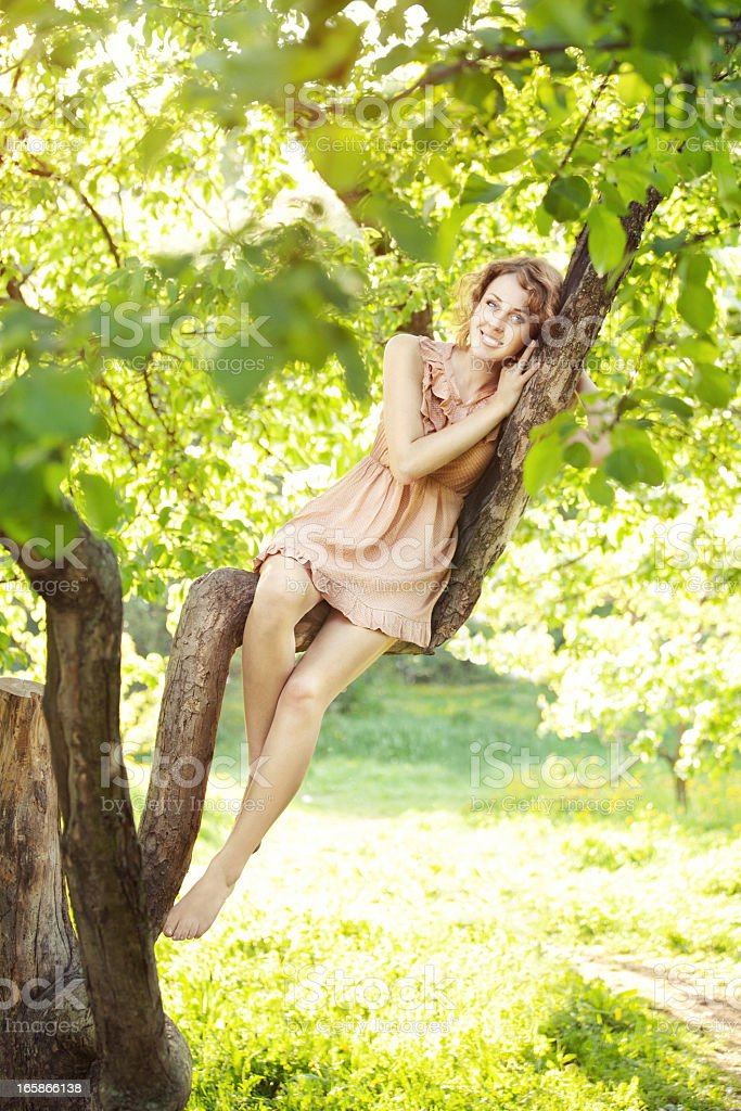 Young beautiful woman sitting on a tree royalty-free stock photo