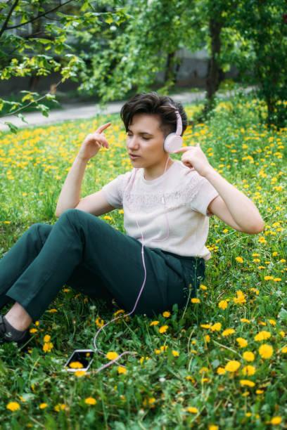 若い美しい女性は、タンポポと芝生緑の草の上に座って、ヘッドフォンで音楽を聴きます。夏の公園でヘッドフォンで音楽を聴く若いgen zの女の子。 - gen z ストックフォトと画像