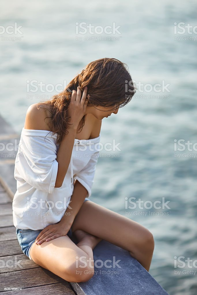 Young beautiful woman sitting on the pier – Foto