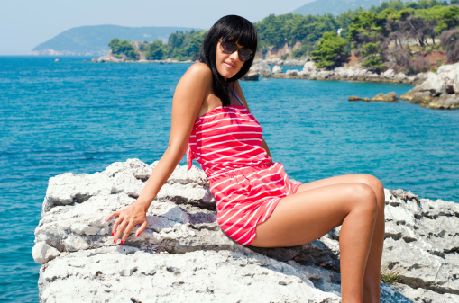 Young beautiful woman sitting on the rock beside sea
