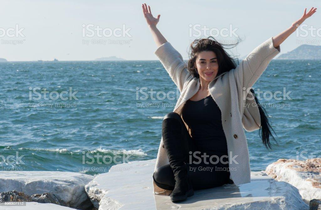 Deniz yanında kayaya oturan genç güzel kadın stok fotoğrafı
