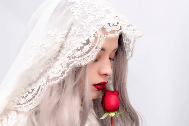 young beautiful woman smelling a red rose. Beautiful woman wearing a white veil. princess or bride smelling roses stock photo