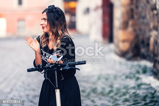 874772840istockphoto Young beautiful woman smiling at camera, posing and enjoying a relaxing evening on city streets 874772874