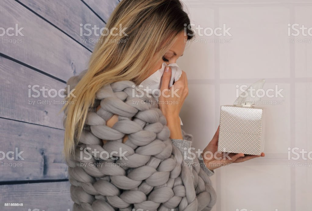 Young beautiful woman Sneezing into Tissue. Flu, Allergy, Runny Nose stock photo